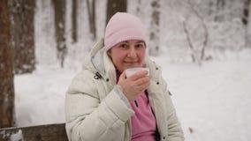 Όμορφη γυναίκα στα έτη που απολαμβάνει τον ελεύθερο χρόνο της στη χειμερινή δασική συνεδρίαση στον ξύλινο πάγκο στον πίνακα Ευτυχ απόθεμα βίντεο