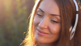 Όμορφη γυναίκα στα ακουστικά που χαμογελούν και που ακούνε τη μουσική Κινηματογράφηση σε πρώτο πλάνο προσώπου Η διάθεση, ευχαρίστ απόθεμα βίντεο