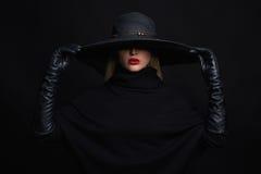 Όμορφη γυναίκα στα γάντια καπέλων και δέρματος οι απεικονίσεις αποκριών στοών μου παρακαλώ βλέπουν παρόμοιο με τη μάγισσα επίσκεψ Στοκ Φωτογραφία