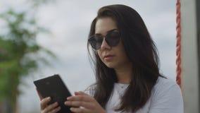 Όμορφη γυναίκα στα γυαλιά ηλίου που διαβάζει ebook υπαίθρια απόθεμα βίντεο