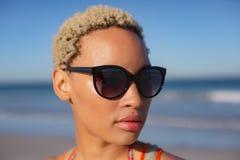 Όμορφη γυναίκα στα γυαλιά ηλίου που κοιτάζει μακριά στην παραλία στην ηλιοφάνεια στοκ φωτογραφία