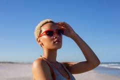 Όμορφη γυναίκα στα γυαλιά ηλίου που κοιτάζει μακριά στην παραλία στην ηλιοφάνεια στοκ φωτογραφίες