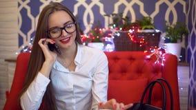 Όμορφη γυναίκα στα γυαλιά που μιλούν στο κινητό τηλέφωνο στον καφέ, 4 Κ Γυναίκα Smartphone που μιλά στο τηλέφωνο καθμένος στον κα φιλμ μικρού μήκους