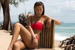 Όμορφη γυναίκα στα γυαλιά ηλίου και κόκκινο μπικίνι στην παραλία η μόδα κοιτάζει κυρία προκλητική Στοκ Φωτογραφία