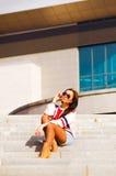 Όμορφη γυναίκα στα γυαλιά ηλίου που κάθεται στα σκαλοπάτια Στοκ Φωτογραφία