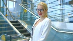 Όμορφη γυναίκα στα γυαλιά και ένα λευκό φόρεμα που στέκεται στα σκαλοπάτια φιλμ μικρού μήκους
