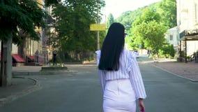 Όμορφη γυναίκα στα μοντέρνα ενδύματα που περπατά στην οδό σε σε αργή κίνηση απόθεμα βίντεο