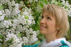 Όμορφη γυναίκα στα λουλούδια ενός δέντρου της Apple Στοκ Φωτογραφία