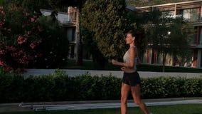 Όμορφη γυναίκα στα σορτς και τοπ τρεξίματα το καλοκαίρι στην οδό απόθεμα βίντεο