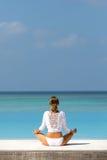 Όμορφη γυναίκα στην άσπρη γιόγκα πρακτικής στην παραλία Μαλδίβες Στοκ Φωτογραφία