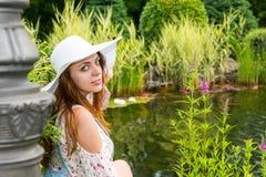 Όμορφη γυναίκα στην άσπρη συνεδρίαση καπέλων κοντά στη λίμνη Στοκ Εικόνες