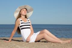 Όμορφη γυναίκα στην άσπρη συνεδρίαση φορεμάτων και καπέλων στην παραλία Στοκ φωτογραφίες με δικαίωμα ελεύθερης χρήσης