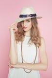 Όμορφη γυναίκα στην άσπρη τοποθέτηση φορεμάτων στο ρόδινο υπόβαθρο στο καπέλο στοκ φωτογραφία