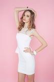 Όμορφη γυναίκα στην άσπρη τοποθέτηση φορεμάτων στο ρόδινο υπόβαθρο στοκ εικόνα