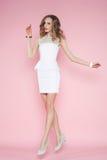 Όμορφη γυναίκα στην άσπρη τοποθέτηση φορεμάτων στο ρόδινο υπόβαθρο στοκ φωτογραφίες με δικαίωμα ελεύθερης χρήσης