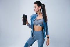 Όμορφη γυναίκα στην αθλητική ένδυση που τίθεται με το μπουκάλι νερό και άκουσμα στη μουσική στα ακουστικά Στοκ Φωτογραφίες