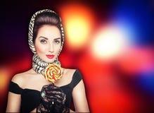 Όμορφη γυναίκα στην αναδρομική καρφίτσα επάνω στο ύφος με το lollipop στο brigh Στοκ εικόνες με δικαίωμα ελεύθερης χρήσης