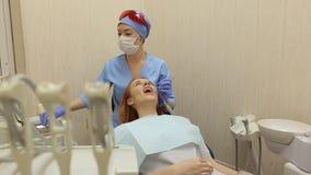 Όμορφη γυναίκα στην επιθεώρηση των δοντιών στην οδοντιατρική φιλμ μικρού μήκους