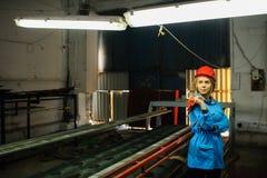 Όμορφη γυναίκα στην κόκκινη εργασία κρανών ασφάλειας ως βιομηχανικό εργάτη Στοκ Εικόνα