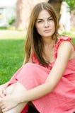 Όμορφη γυναίκα στην κόκκινη συνεδρίαση φορεμάτων στο πάρκο Στοκ Φωτογραφίες