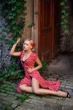 Όμορφη γυναίκα στην κόκκινη τοποθέτηση φορεμάτων στην οδό στοκ εικόνες