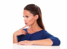 Όμορφη γυναίκα στην μπλε μπλούζα που κοιτάζει στο δικαίωμά της Στοκ Εικόνες