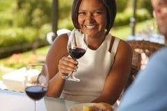 Όμορφη γυναίκα στην οινοποιία με ένα ποτήρι του κόκκινου κρασιού στοκ εικόνα