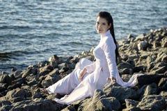 Όμορφη γυναίκα στην παραδοσιακή χαλάρωση πολιτισμού του Βιετνάμ στη λίμνη εκτός από το μπλε νερό Στοκ εικόνα με δικαίωμα ελεύθερης χρήσης