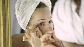 Όμορφη γυναίκα στην πετσέτα που μαδά τα φρύδια της Φροντίδα δέρματος και home Spa απόθεμα βίντεο
