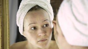 Όμορφη γυναίκα στην πετσέτα που μαδά τα φρύδια της Φροντίδα δέρματος και home Spa φιλμ μικρού μήκους