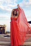 Όμορφη γυναίκα στην πολυτελή κόκκινη τοποθέτηση φορεμάτων στο πάρκο Στοκ φωτογραφίες με δικαίωμα ελεύθερης χρήσης