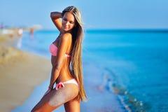 Όμορφη γυναίκα στην προκλητική χαλάρωση μπικινιών στη θερινή παραλία Στοκ Εικόνες