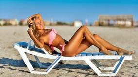 Όμορφη γυναίκα στην προκλητική χαλάρωση μπικινιών στη θερινή παραλία Στοκ Φωτογραφία