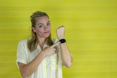Όμορφη γυναίκα στη βιασύνη που δείχνει το χρόνο ρολογιών, ανυπομονησία, που ανατρέπεται καιη για την καθυστέρηση προθεσμίας στοκ φωτογραφία
