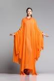 Όμορφη γυναίκα στη μακροχρόνια πορτοκαλιά τοποθέτηση φορεμάτων δραματική στο στούντιο στοκ εικόνες