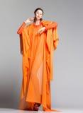 Όμορφη γυναίκα στη μακροχρόνια πορτοκαλιά τοποθέτηση φορεμάτων δραματική στο στούντιο Στοκ Εικόνα