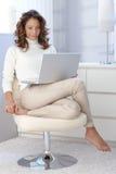 Όμορφη γυναίκα στη σύγχρονη έδρα με το lap-top Στοκ εικόνες με δικαίωμα ελεύθερης χρήσης