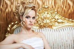 Όμορφη γυναίκα στη χρυσή πολυθρόνα Στοκ φωτογραφία με δικαίωμα ελεύθερης χρήσης