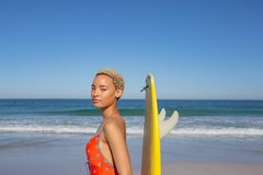 Όμορφη γυναίκα στη swimwear στάση με την ιστιοσανίδα στην παραλία στην ηλιοφάνεια στοκ φωτογραφίες