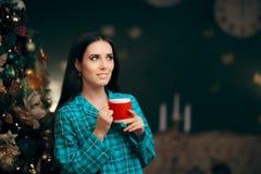 Όμορφη γυναίκα στις πυτζάμες με το ζεστό ποτό δίπλα στο χριστουγεννιάτικο δέντρο της Στοκ Εικόνες