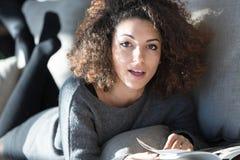 Όμορφη γυναίκα στον καναπέ με το περιοδικό Στοκ Εικόνες