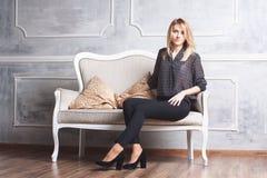 Όμορφη γυναίκα στον καναπέ στο εσωτερικό Στοκ Εικόνες
