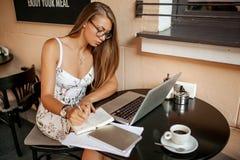 Όμορφη γυναίκα στον καφέ με το lap-top που παίρνει τις σημειώσεις στοκ φωτογραφία με δικαίωμα ελεύθερης χρήσης