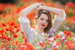 Όμορφη γυναίκα στον τομέα των κόκκινων λουλουδιών παπαρουνών, χρόνος άνοιξη Στοκ Εικόνα