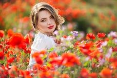 Όμορφη γυναίκα στον τομέα των κόκκινων λουλουδιών παπαρουνών, χρόνος άνοιξη Στοκ Φωτογραφίες