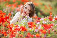 Όμορφη γυναίκα στον τομέα των κόκκινων λουλουδιών παπαρουνών, χρόνος άνοιξη Στοκ εικόνα με δικαίωμα ελεύθερης χρήσης