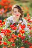 Όμορφη γυναίκα στον τομέα των κόκκινων λουλουδιών παπαρουνών, χρόνος άνοιξη Στοκ Εικόνες