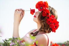 Όμορφη γυναίκα στον τομέα των κόκκινων λουλουδιών παπαρουνών, χρόνος άνοιξη Στοκ φωτογραφία με δικαίωμα ελεύθερης χρήσης