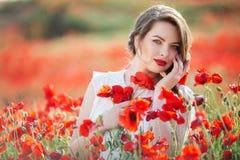Όμορφη γυναίκα στον τομέα των λουλουδιών παπαρουνών, χρόνος άνοιξη Στοκ Φωτογραφίες