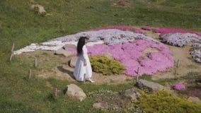 Όμορφη γυναίκα στους πολύ άσπρους περιπάτους φορεμάτων στο βοτανικό κήπο απόθεμα βίντεο